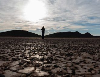 Ein Junge fotografiert einen ausgetrockneten Salzsee im Sanbona Game Reserve