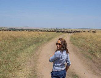Frau vor Gnuherde in der Masai Mara während einer Kenia Safari Reise