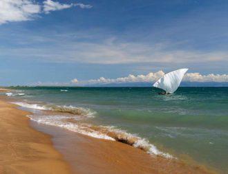 menschenleerer Strand mit einem kleinem Boot im Wasser am Lake Tanganyika